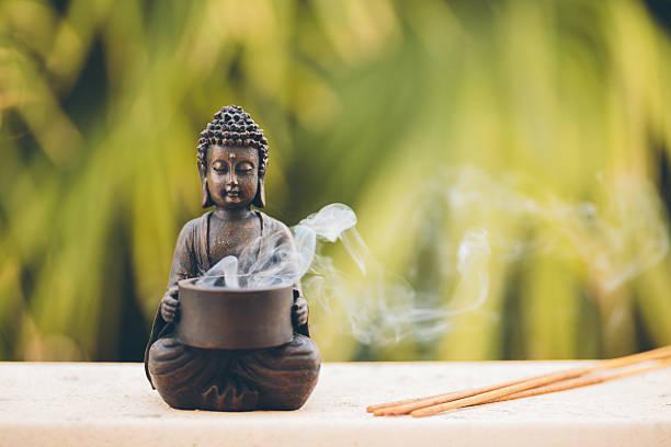 buddha figurine with incense - buddha stockfoto's en -beelden