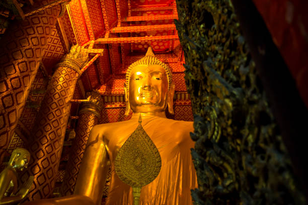 Buddha golden sculpture on lightened gold background in temple stock photo