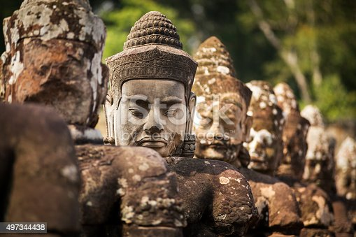 In a row, a newly made Buddhist head stands out from the other ancient statues. Situated along the road leading to the gate of Angkor Thom temple, there has been substantial renovation work in Angkor Wat UNESCO Heritage site. Selective focus on the new stone head.