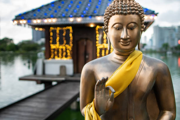 Buddha in a dharmachakra mudra pose Buddha made of bronze in a dharmachakra mudra pose, in front of a temple on the Beira Lake in Colombo, Sri Lanka. bodhisattva stock pictures, royalty-free photos & images