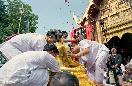 istock Buddha Phra Singh of Phra Singh temple was moved to the parade cars for pour water in Songkran festival 693637204