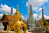 Wide angled view of Buddha sculpture Kinora or Kinnaree ( mythological creature, half bird, half man ) at Wat Phra Kaeo and Grand Palace in Bangkok, Thailand. Many details of Grand Palace in the background, also visible are beautiful cloudscape with blue sky and cumulus clouds on one sunny day in Bangkok.