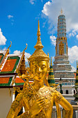 Buddha sculpture Kinnaree or Kinora ( mythological creature, half bird, half man ) at Wat Phra Kaeo and Grand Palace in Bangkok, Thailand. Many details of Grand Palace in the background, also visible are beautiful cloudscape with blue sky and cumulus clouds on one sunny day in Bangkok.