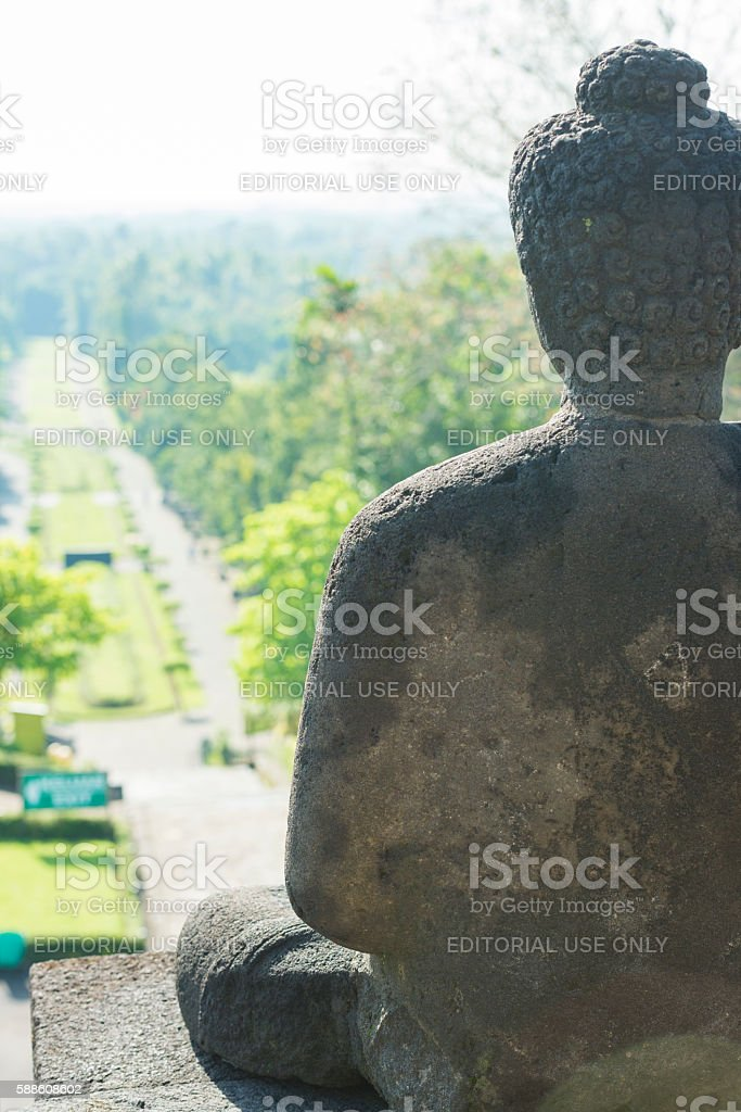 Buddha Sculture with Palm Trees in Ancient Indonesian Borobudur Temple stock photo
