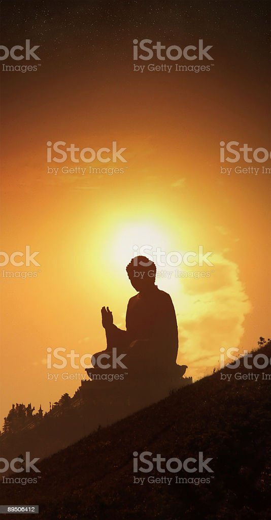 Buddha statue at sunset with flaming sun and starscape royalty-free stock photo