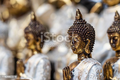 Buddha statue figures souvenir on display for sale on street market in Ubud, Bali, Indonesia. Handicrafts and souvenir shop display, close up
