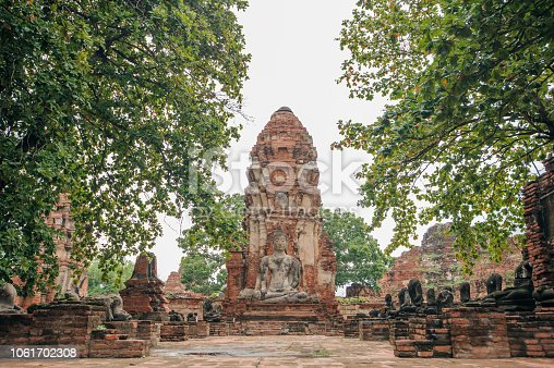 Buddha statue in front of broken pagoda