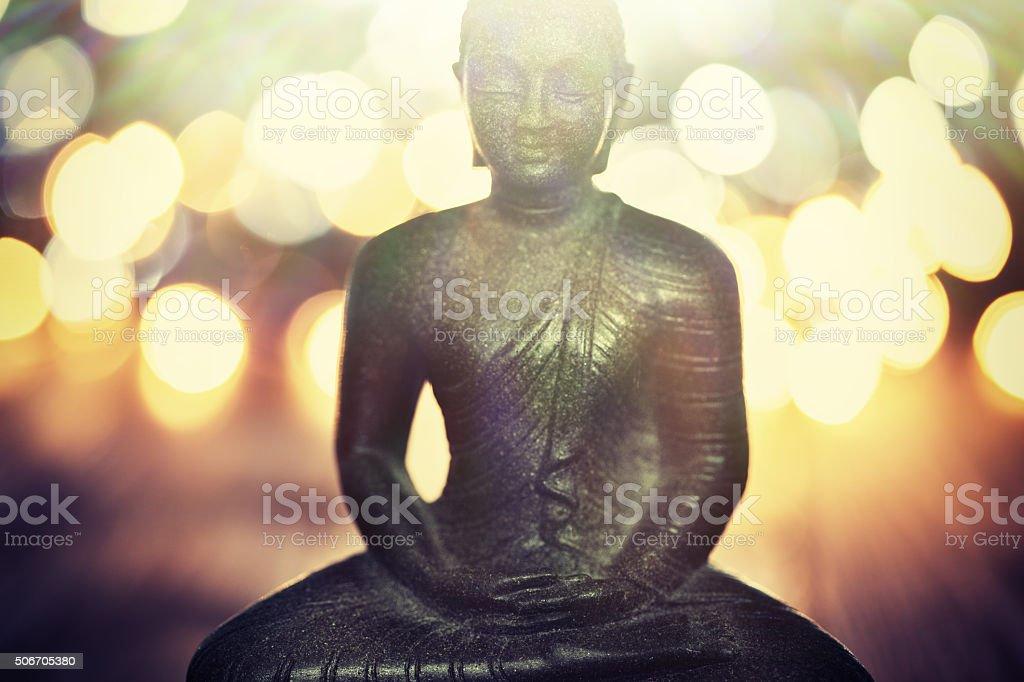 Buddha statue on blurred lights background stock photo