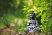 istock Buddha statue outside on nature and green background with copy space 1222066739