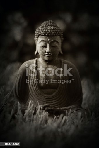Statue of Buddha in meditation on black background. Mass-produced lava stone replica.