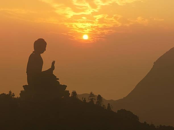 Buddha statue silhouette at sunset stock photo