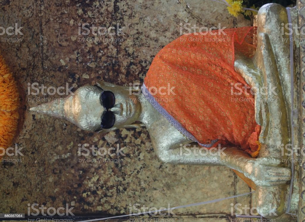 A Buddha statue wears sunglasses stock photo