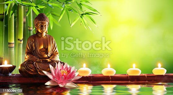 Buddha Golden Statue With Candles In Green Background