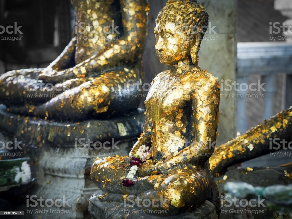 Buddha statue with golden leaf. stock photo