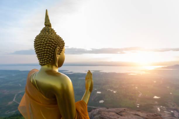Buddha statue with sunrise and Pa Sak Jolasid Dam stock photo
