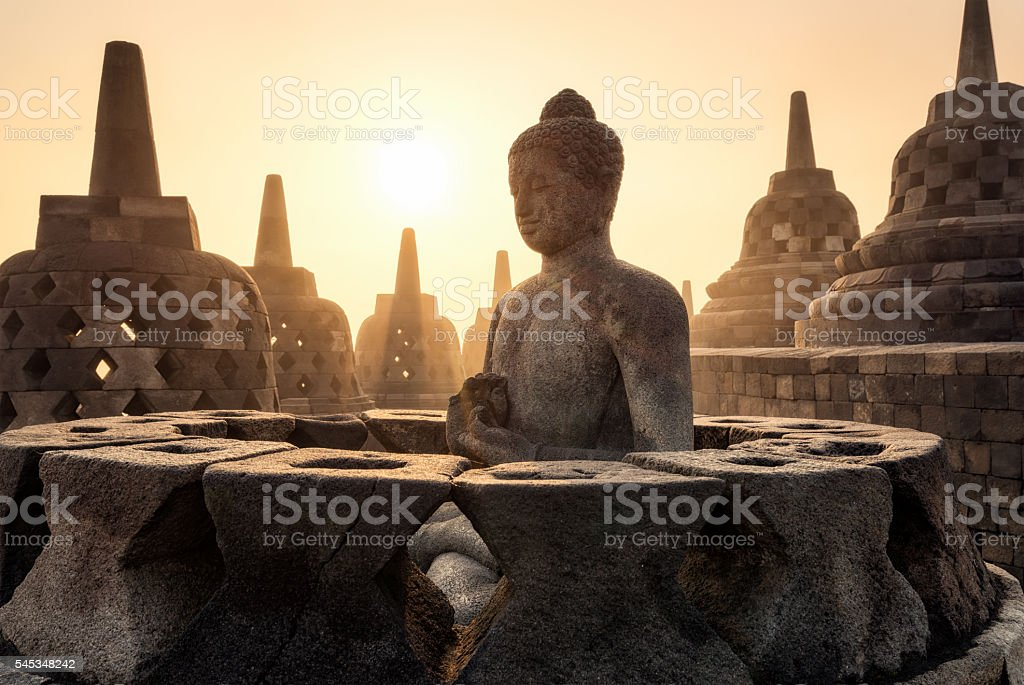 Buddha statue with sunshine through pagodas at Borobudur, Indonesia stock photo