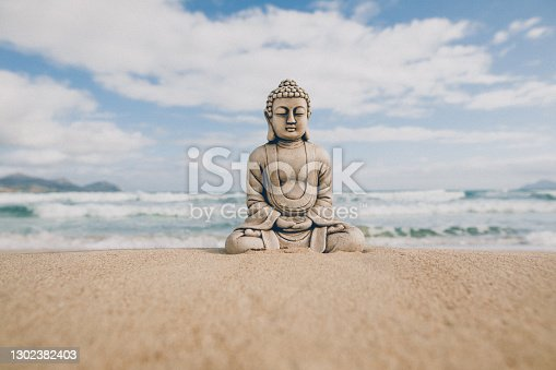 istock Buddha stone figure sitting on the seashore in front of the slightly rough sea 1302382403