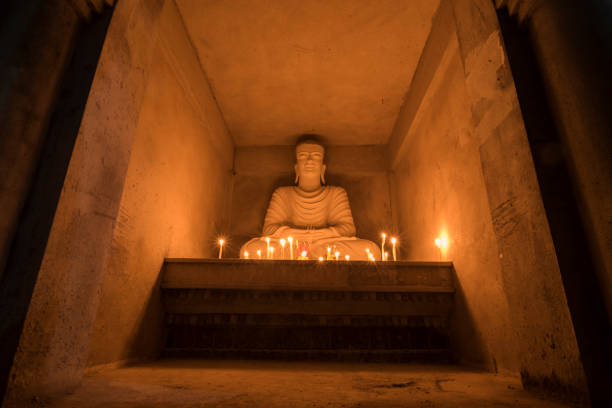 buddha with bright candles in a brick wall. - makha bucha stock photos and pictures