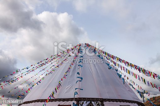 Buddhism symbol prayer flags on white yurt tent blue cloudy sky background. Religious concept