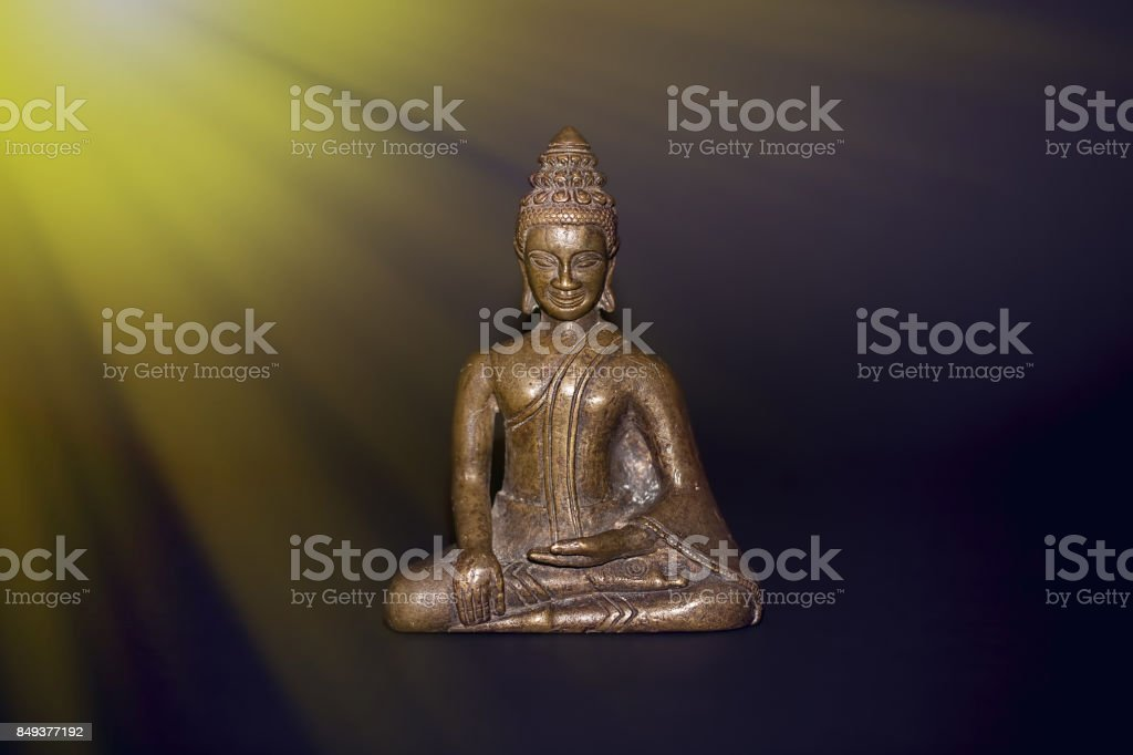 Buddhist meditation. Traditional bronze buddha meditating in rays of divine light. Zen buddhism and spiritual enlightenment or awakening. stock photo