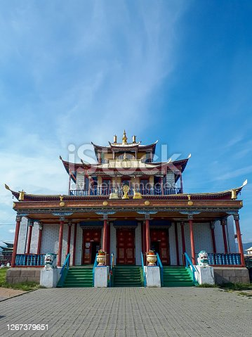 Buddhist monastery temple beautiful religious building with colorful wood carvings symbolic ornaments floral clouds with golden animal statues on the roof with summer bright blue sky. Ivolgynsky datsan, Buryatia, Siberia, Russia
