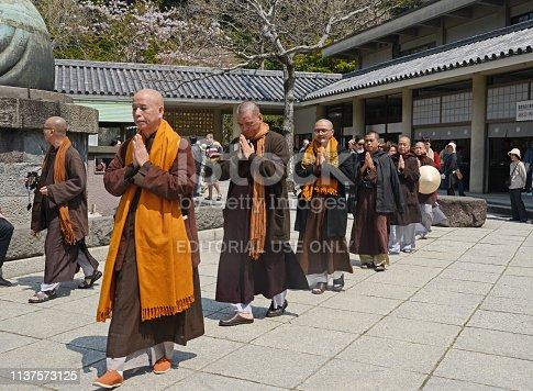 Kamakura, Japan - April 10, 2014: The buddhist monks in courtyard praying a monastery in Kamakura