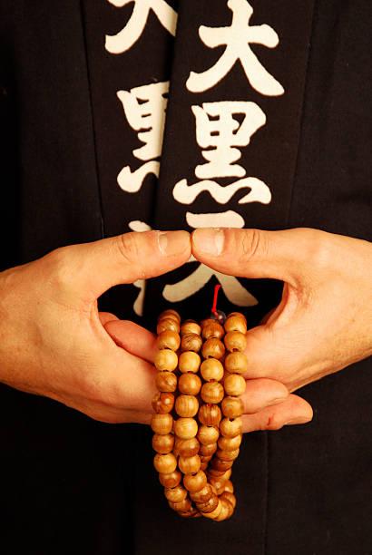 buddhist monk holding prayer beads stock photo