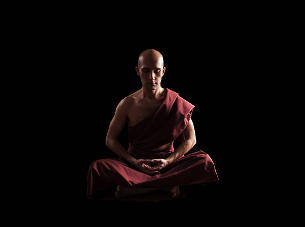 buddhist monk in meditation pose over black background - hermano fotografías e imágenes de stock