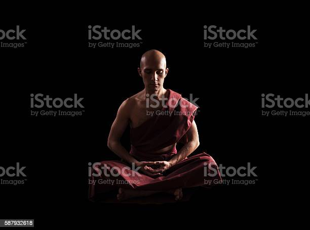 buddhist monk in meditation pose over black background