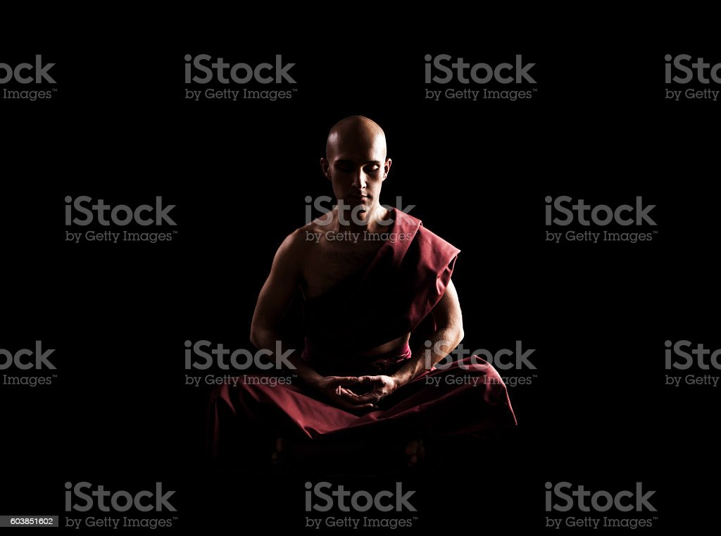 buddhist monk in meditation pose over black background stock photo