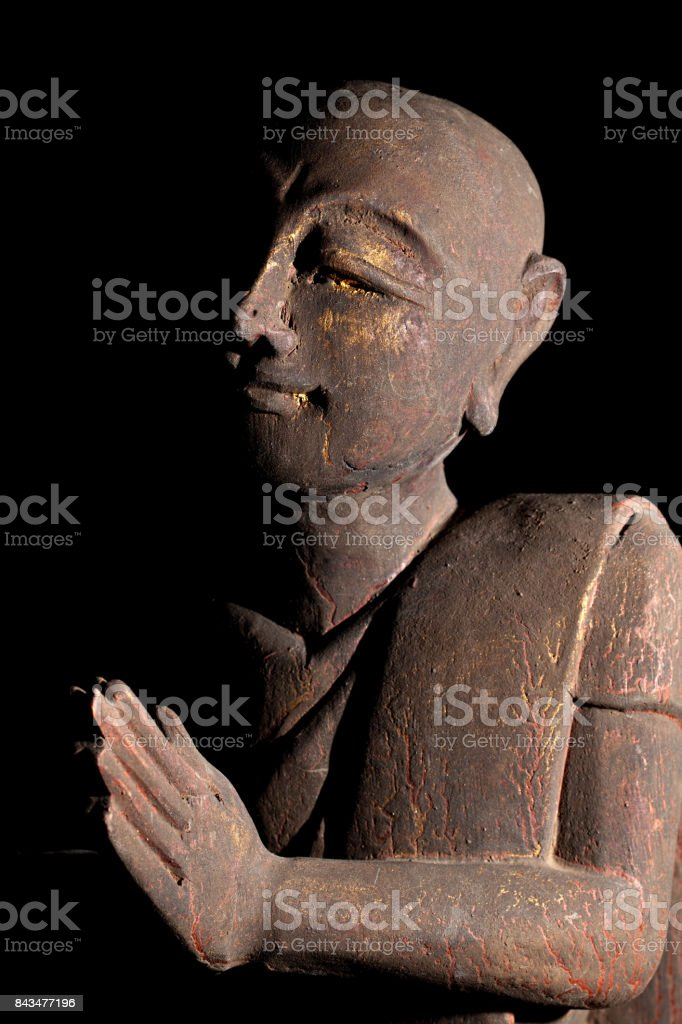 Buddhist monk in serene prayer pose. stock photo