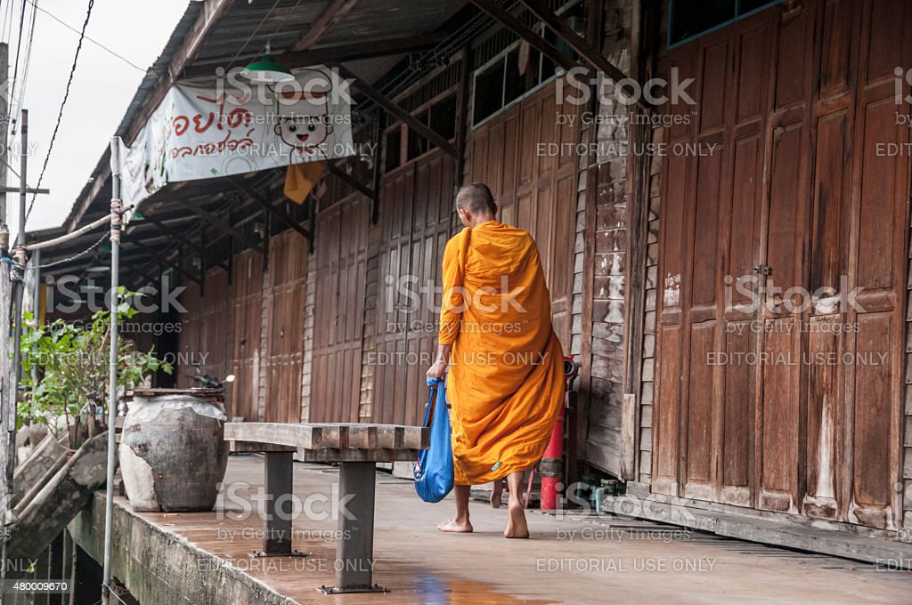 Buddhist Monk Amphawa, Thailand - July 22, 2011: A Buddhist monk on his daily alms round at Amphawa in Thailand. In Theravada Buddhism, monks go on a daily alms round (or pindacara) in the morning to collect food. This is thought to make merit for the giver 2011 Stock Photo