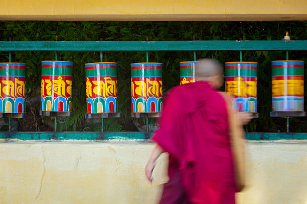 Buddhist monk rotating prayer wheels in McLeod Ganj Buddhist monk passing and rotating prayer wheels on kora around Tsuglagkhang complex in McLeod Ganj, Himachal Pradesh, India circumambulation stock pictures, royalty-free photos & images