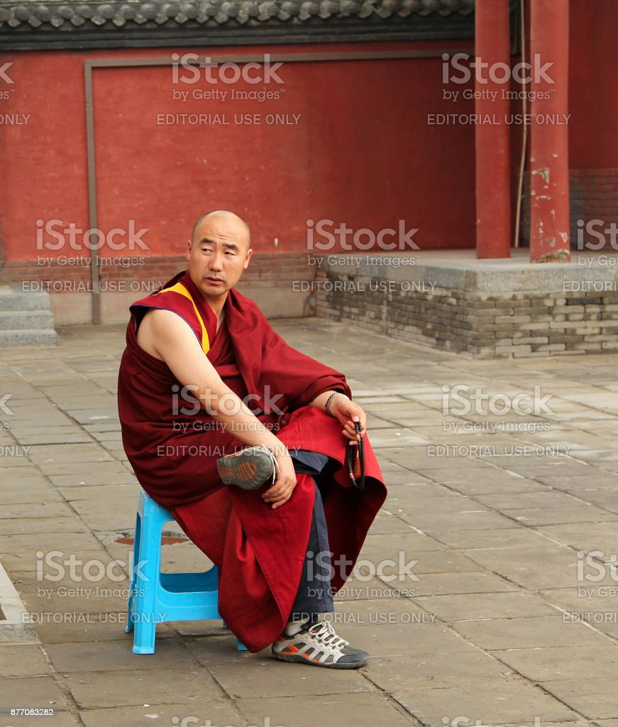 Buddhist monk with rosary sitting in the yard of Dazhao Monastery stock photo