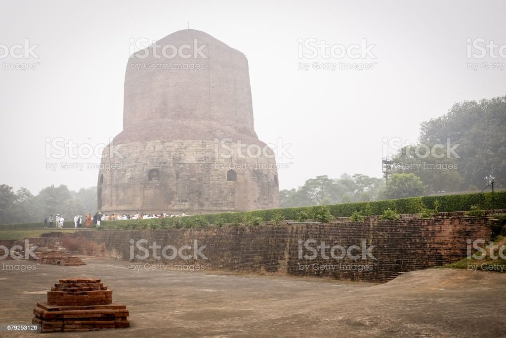 VARANASI, INDIA - DECEMBER 2, 2016: Buddhist monks and tourists come to visit and pray in the misty morning at Dhamekh Stupa, the Buddhist historic landmark of Sarnath, Varanasi, India. photo libre de droits
