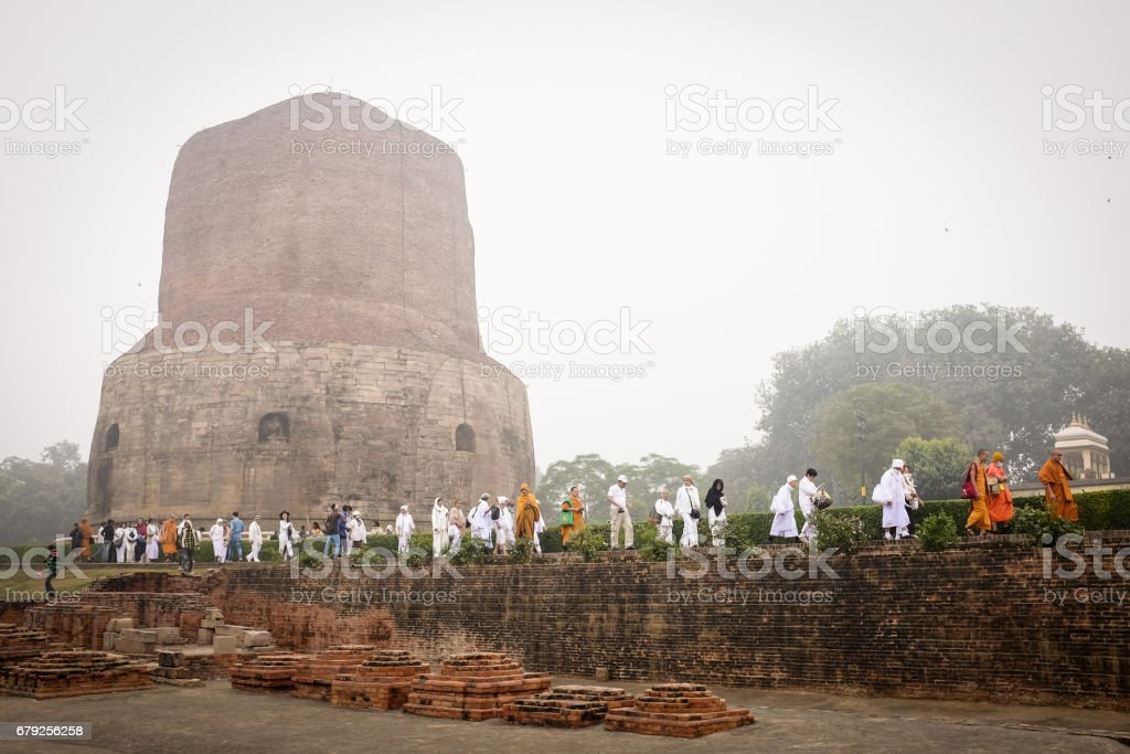 VARANASI, INDIA - DECEMBER 2, 2016: Buddhist monks and tourists come to visit and pray in the misty morning at Dhamekh Stupa, the Buddhist historic landmark of Sarnath, Varanasi, India. stock photo