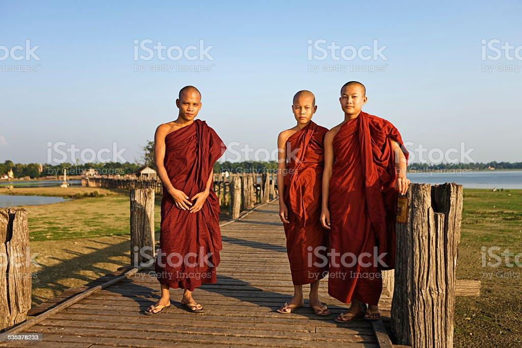 Buddhist Monks crossing U Bein Bridge stock photo