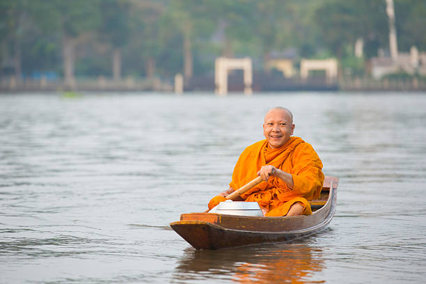 buddhist monks in boat - row of heads stock photos and pictures