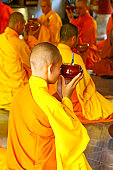 Hue, Vietnam - June 5, 2006: Buddhist monks in a Central Vietnam monastery pray before beginning their simple meal.