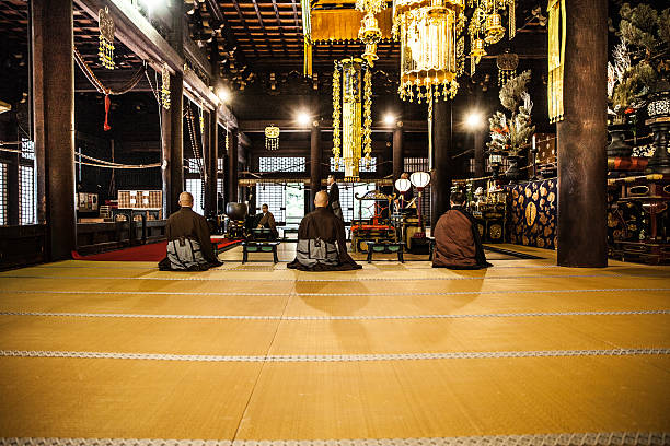 buddhist monks praying in early morning inside a temple - 寺院 ストックフォトと画像