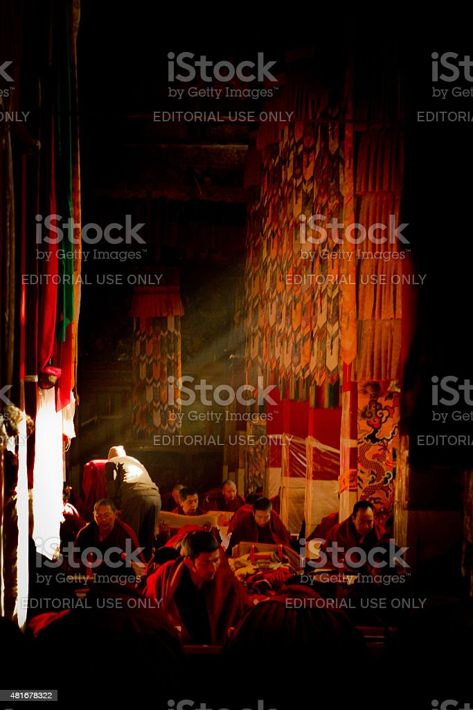 Buddhist monks study in sunbeams within Drepung Monastery, Lhasa, Tibet stock photo