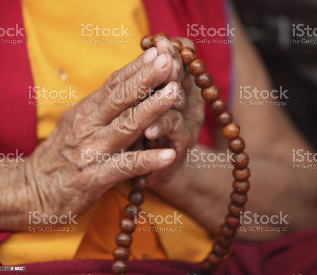 Buddhist Nun praying with Mala Prayer beads stock photo
