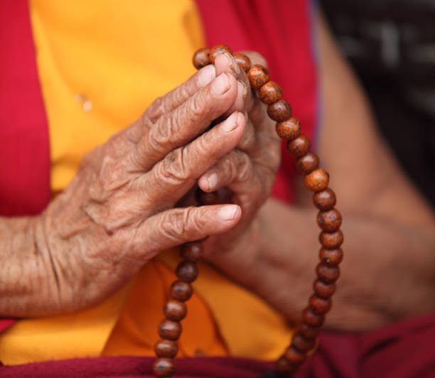 Buddhist Nun praying with Mala Prayer beads stock photo
