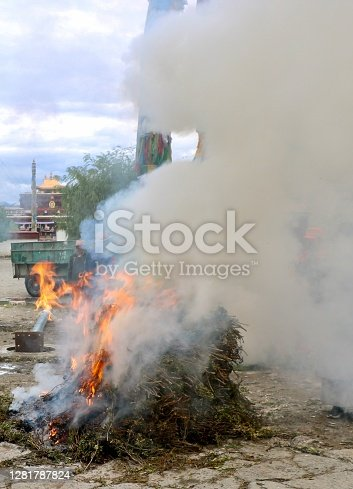 The photo shows juniper sprigs burnt by pilgrims as offers, in front of a Buddhist monastery on the Tibetan plateau.