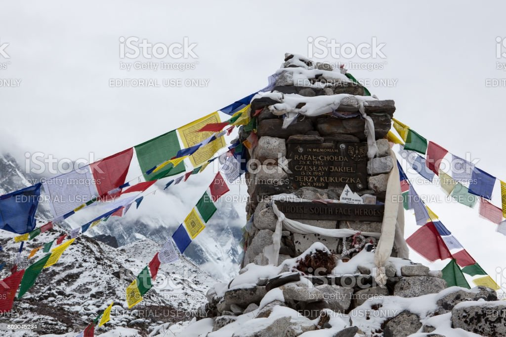 Buddhist prayer flags under snow on a chorten memorial to honor the great polish climber Jerzy Kukuczka and other heroes of the Lhotse South Face. stock photo
