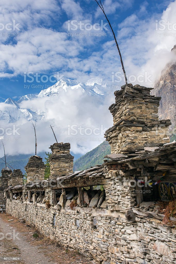 Buddhist prayer mani wall with prayer wheels in nepalese village stock photo