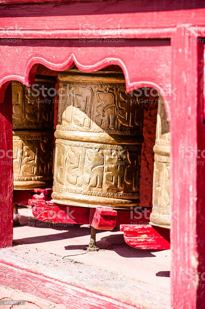 Buddhist prayer wheels in Tibetan monastery with written mantra. India, royalty-free stock photo