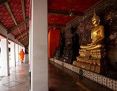 Bangkok, Thailand - July 14, 2013: Buddhist priest and Golden Buddha at corridor at Wat Suthat temple, Bangkok, Thailand