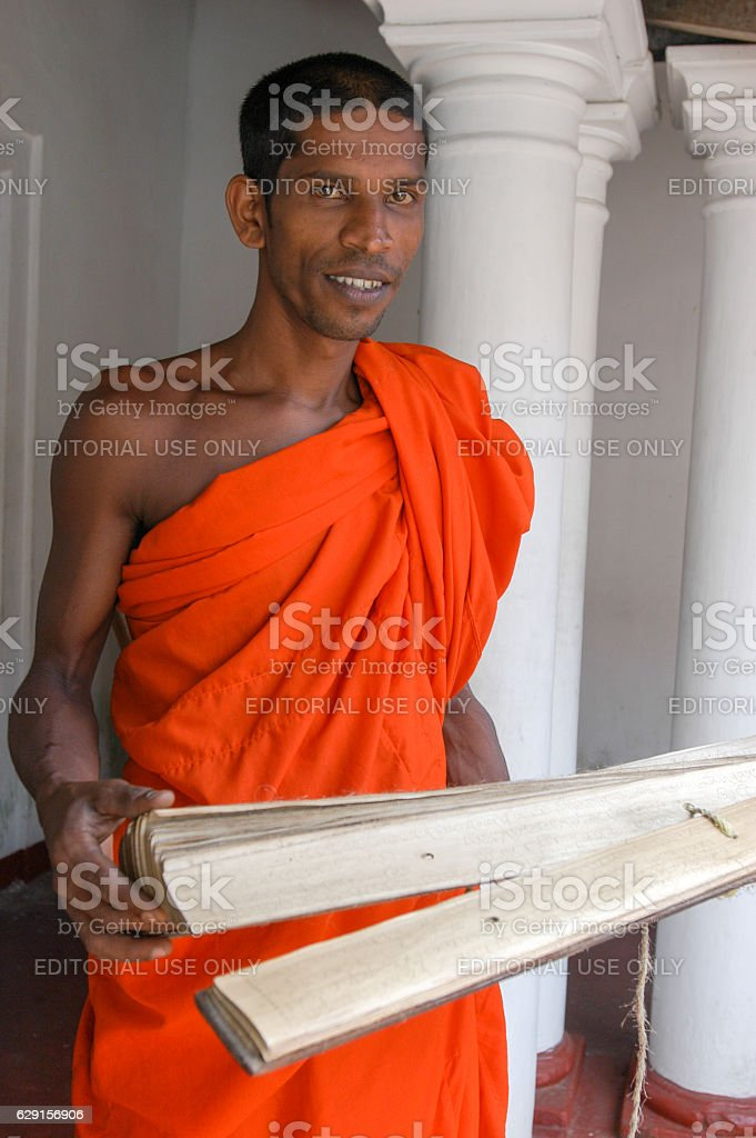 Buddhist priest with holy scriptures stock photo