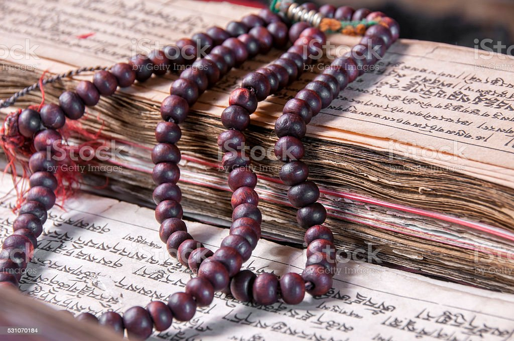 Buddhist religious japa mala on manuscript stock photo